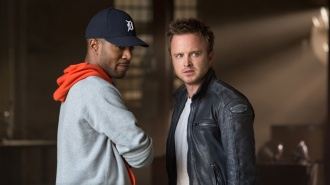 NFS-D030-20567 Aaron Paul (right) with Scott Mescudi (Kid Cudi) in DreamWorks Pictures' NEED FOR SPEED. The story chronicles a near-impossible cross-country race against time-one that begins as a mission for revenge, but proves to be one of redemption. In a last attempt to save his struggling garage, blue-collar mechanic Tobey Marshall (Aaron Paul)-who with his team, including Benny (Scott Mescudi), skillfully builds and races muscle cars on the side.